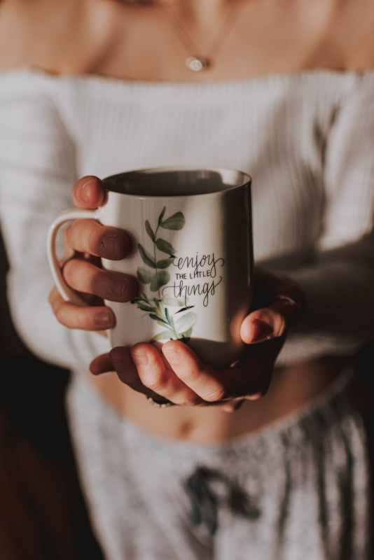A woman's hands holding a mug which says 'enjoy the little things'